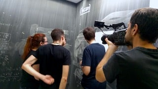 cameraman is filming students writing formulas on a big blackboard in Bilbao